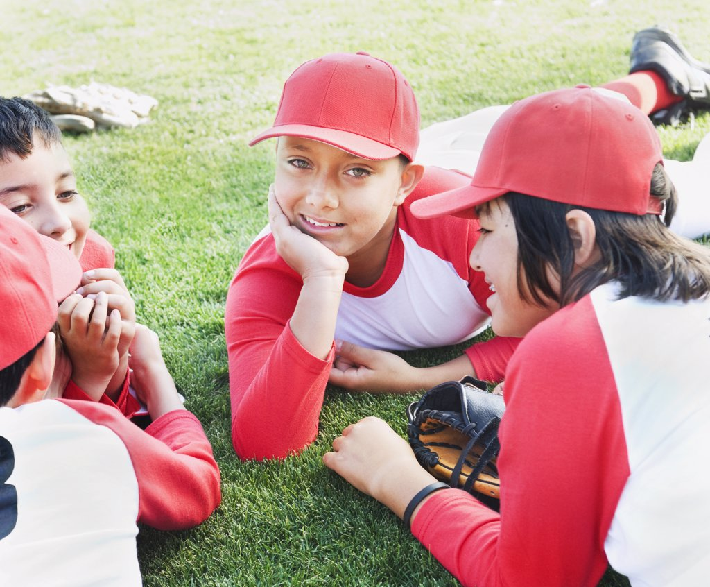Stock Photo: 1589R-62554 Multi-ethnic boys in baseball uniforms laying on grass