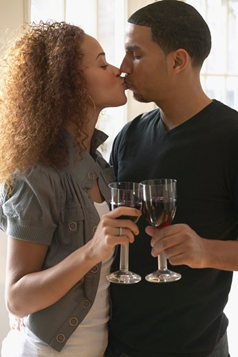 Multi-ethnic couple holding wine glasses and kissing : Stock Photo