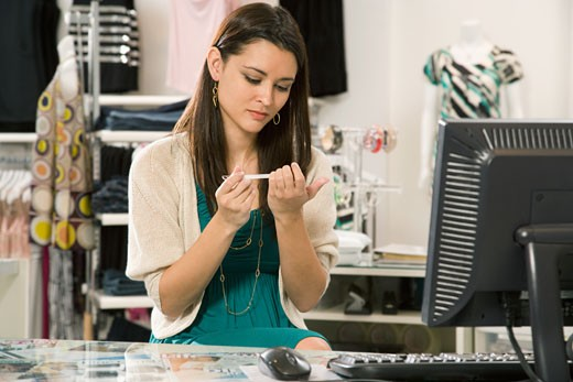 Stock Photo: 1589R-62820 Mixed race cashier filing nails in clothing shop
