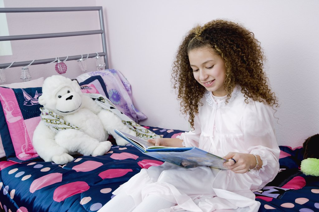 Mixed race girl reading bedtime story : Stock Photo