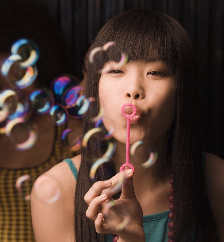 Stock Photo: 1589R-63187 Asian woman blowing bubbles