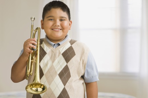 Hispanic boy holding trumpet : Stock Photo