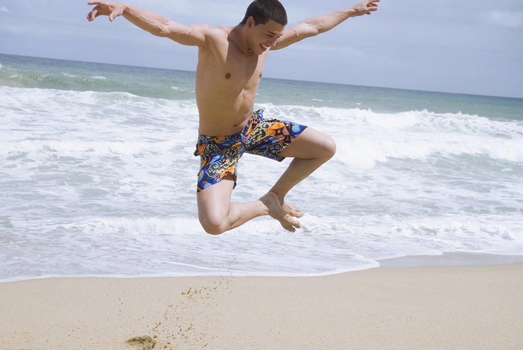 Stock Photo: 1589R-63599 Hispanic man at beach jumping in mid-air
