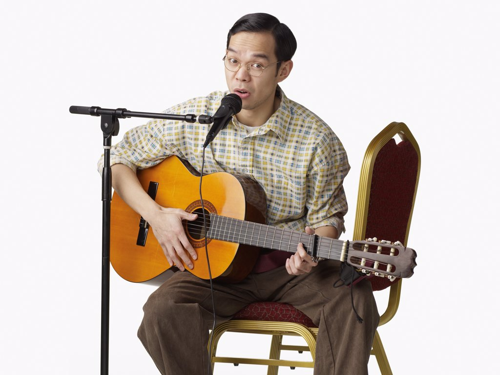 Stock Photo: 1589R-63900 Asian man playing guitar and singing