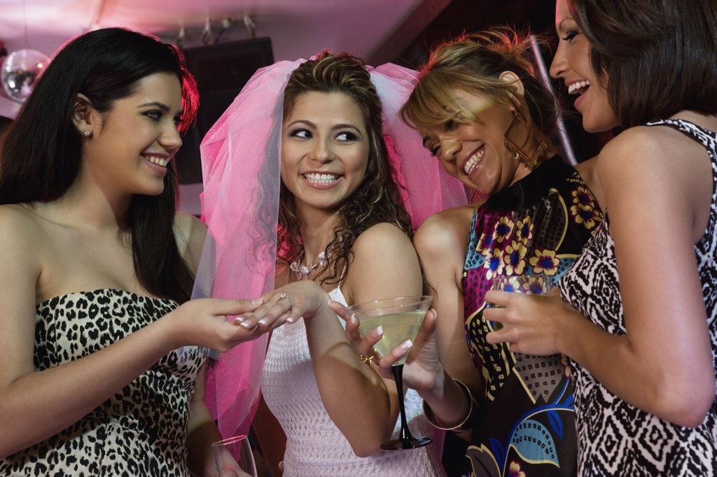 Stock Photo: 1589R-64024 Friends admiring woman's engagement ring in nightclub