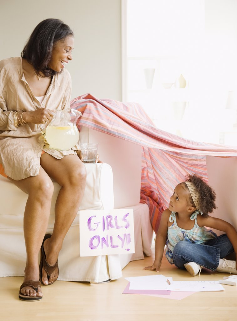 Stock Photo: 1589R-64099 African grandmother offering granddaughter lemonade