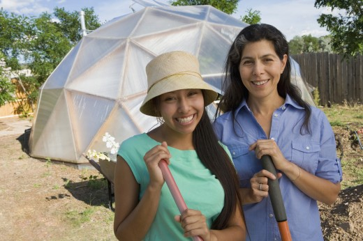 Stock Photo: 1589R-64169 Mother and daughter gardening near conservatory
