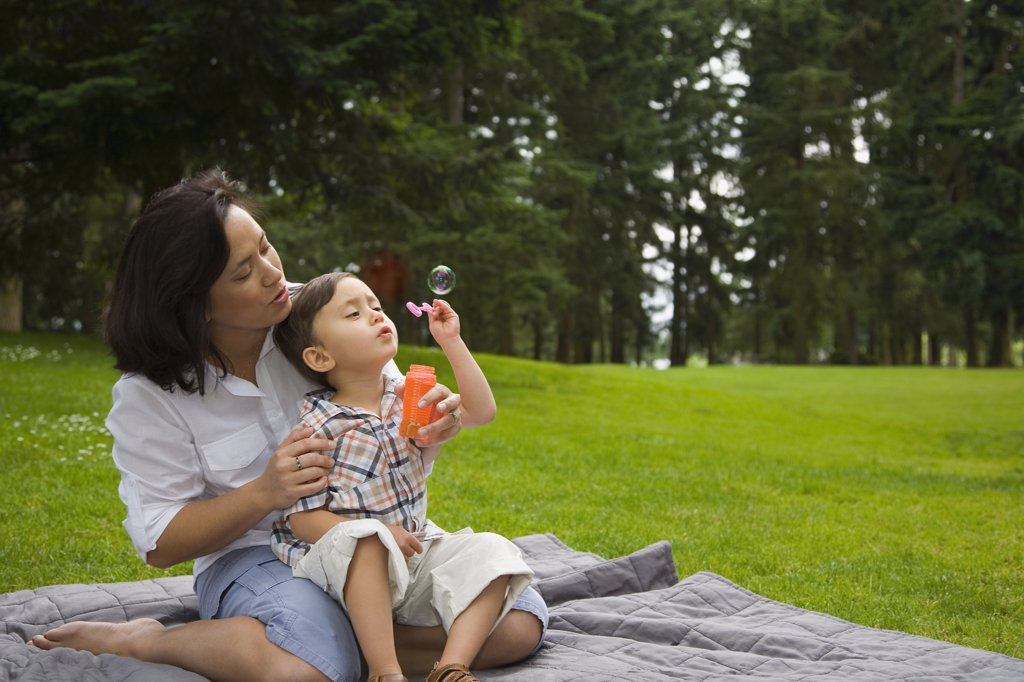Boy blowing bubbles in park with mother : Stock Photo