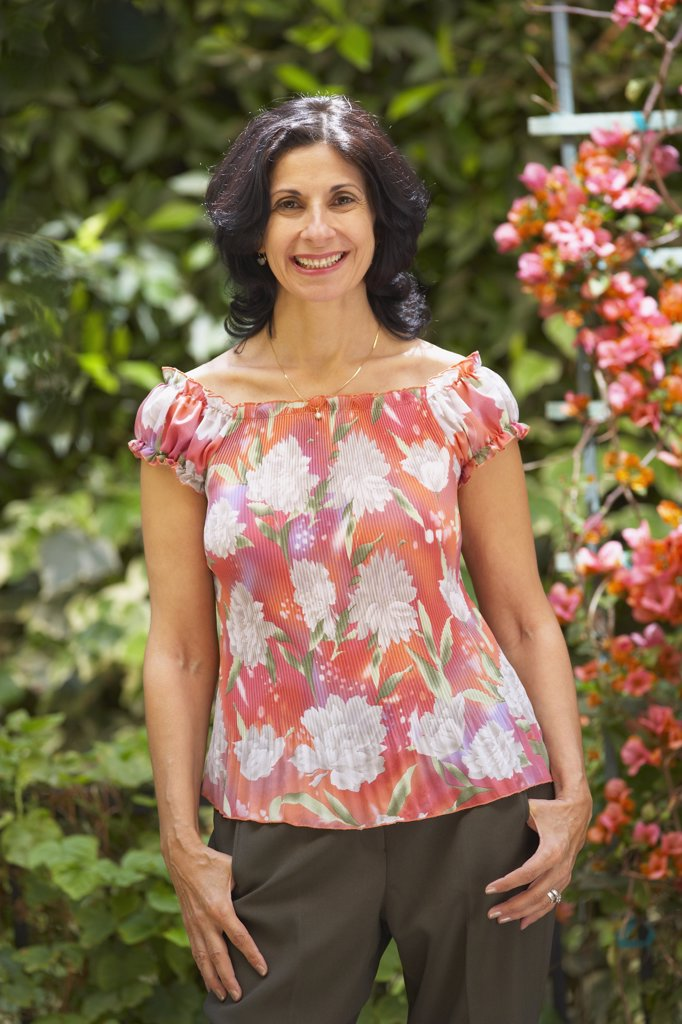 Confident Middle Eastern woman standing in garden : Stock Photo