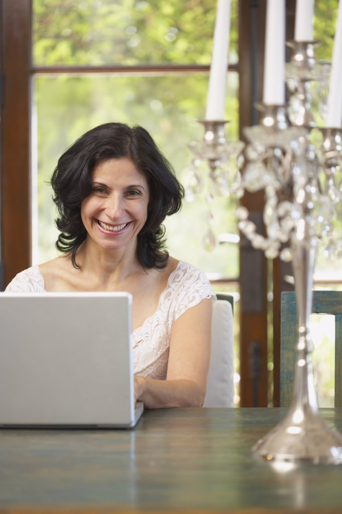 Confident Middle Eastern woman typing on laptop in dining room : Stock Photo