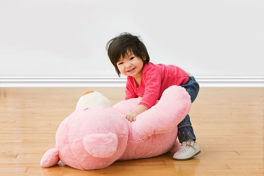 Stock Photo: 1589R-64530 Mixed race girl picking up large teddy bear