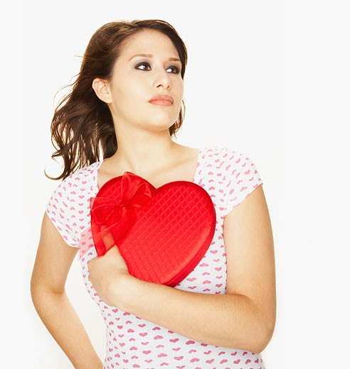 Pacific Islander woman holding heart-shaped box : Stock Photo