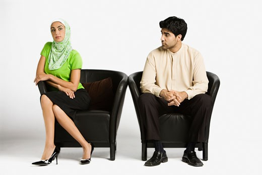 Middle Eastern man and woman sitting in chairs : Stock Photo