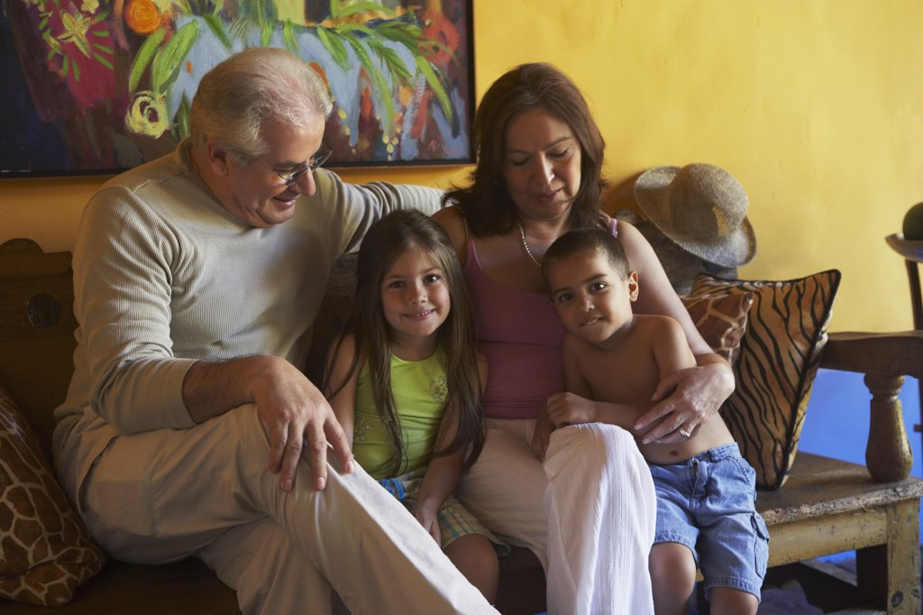 Hispanic grandparents sitting with grandchildren : Stock Photo