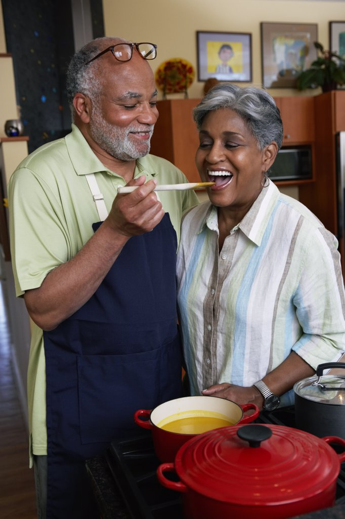Stock Photo: 1589R-65025 African woman tasting husband's cooking