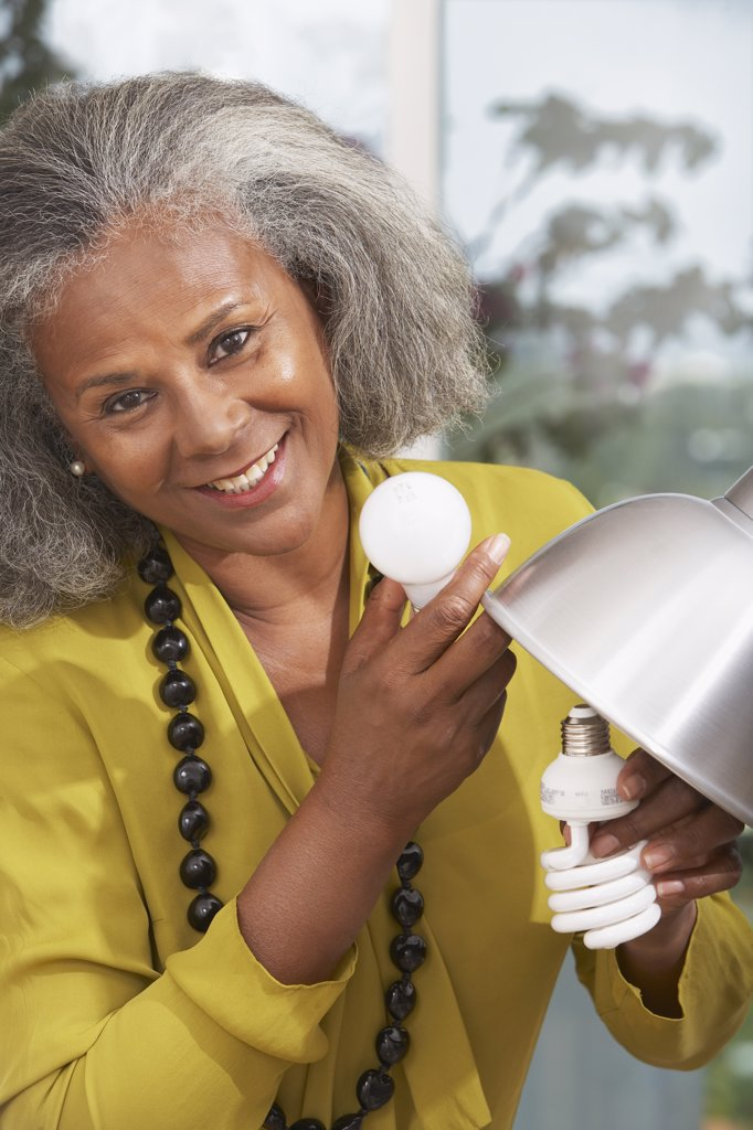 African woman changing lightbulb at home : Stock Photo
