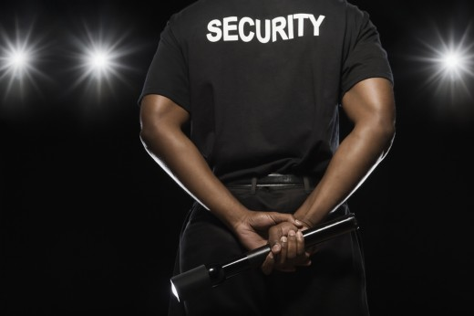 African security guard holding flashlight : Stock Photo