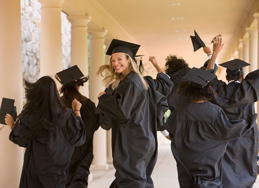 Excited graduating students in caps and gowns : Stock Photo