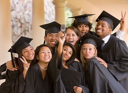 Graduating classmates taking self-portrait with cell phone : Stock Photo
