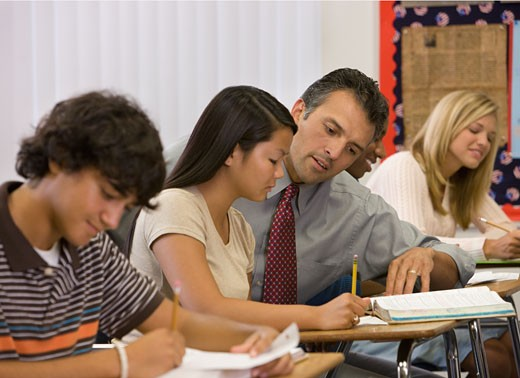 Stock Photo: 1589R-65274 Teacher helping student with homework in classroom