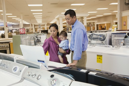 Stock Photo: 1589R-65281 Couple viewing washing machines in appliance showroom