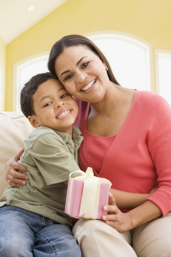 Stock Photo: 1589R-65329 African boy giving mother a present