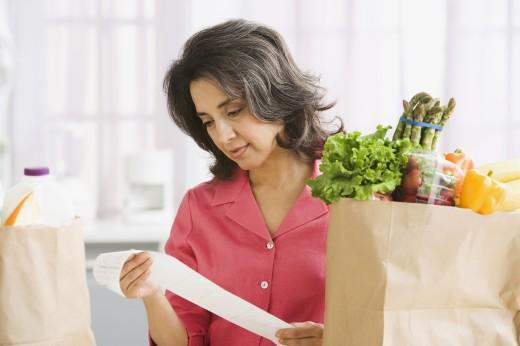 Hispanic woman checking grocery receipt : Stock Photo