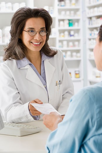 Stock Photo: 1589R-65398 Hispanic pharmacist filling prescription