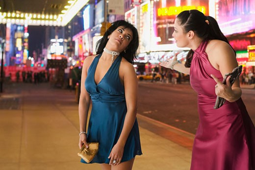 Stock Photo: 1589R-65478 Hispanic friends arguing on sidewalk at night