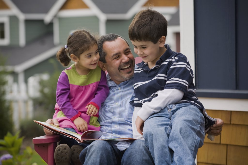 Father reading to son and daughter on porch : Stock Photo