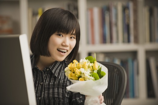 Asian businesswoman holding bouquet at desk : Stock Photo