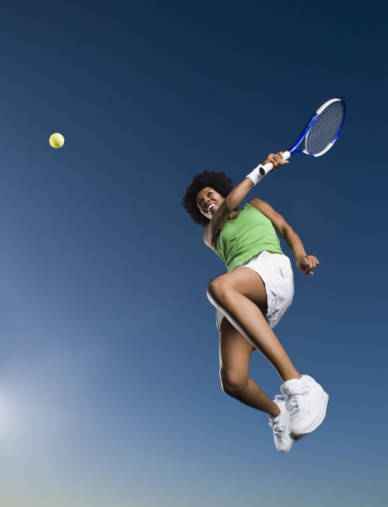 African woman playing tennis in mid-air : Stock Photo