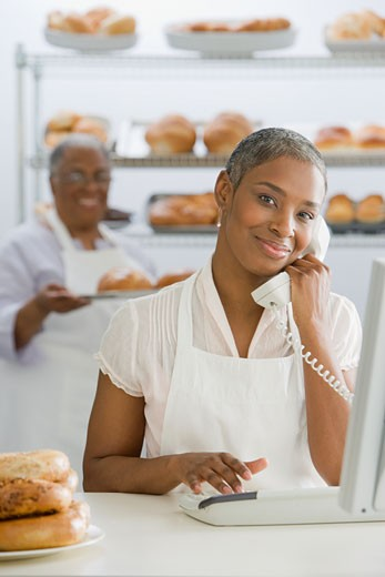 Stock Photo: 1589R-68800 African woman using telephone in bakery