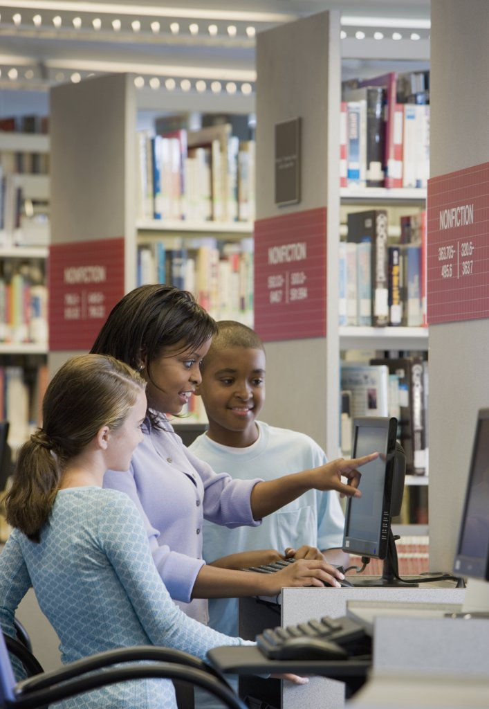 Stock Photo: 1589R-68836 Teacher and students researching in library