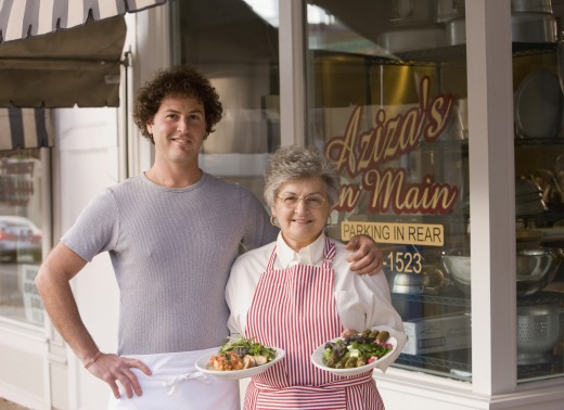 Cook and waitress posing in front of restaurant : Stock Photo