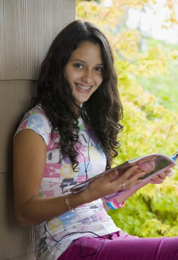 Smiling Hispanic teenage girl reading outdoors : Stock Photo
