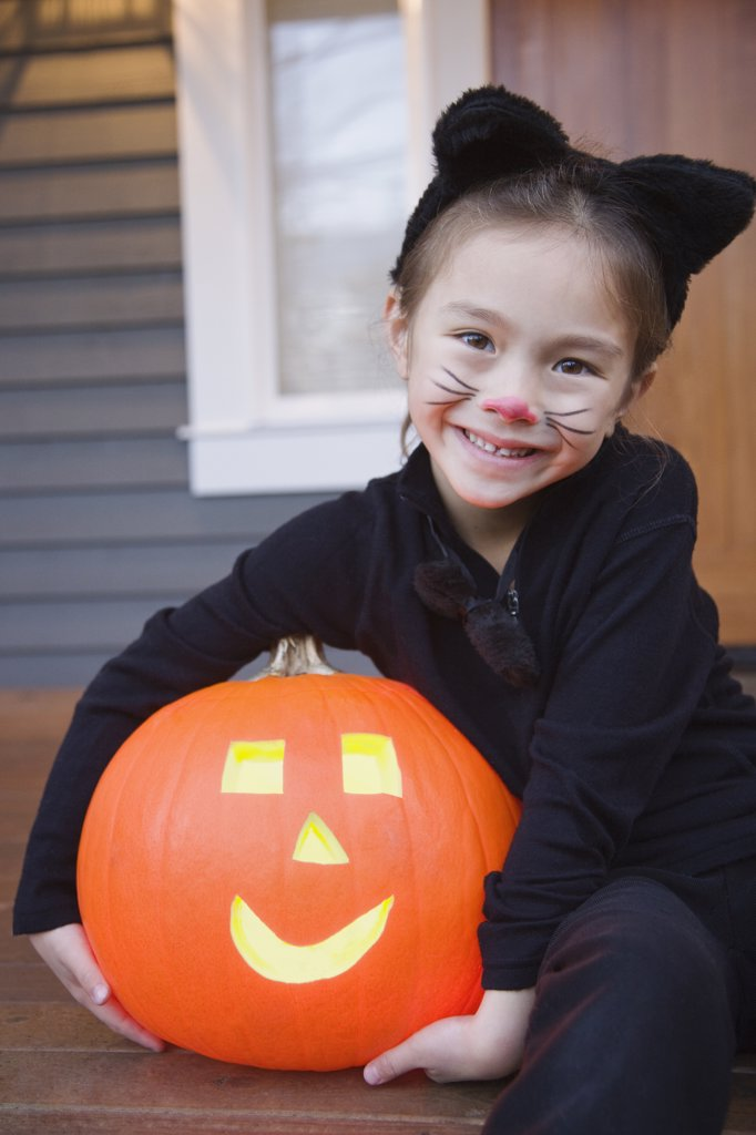 Stock Photo: 1589R-69009 Mixed race young girl in cat costume holding Halloween pumpkin