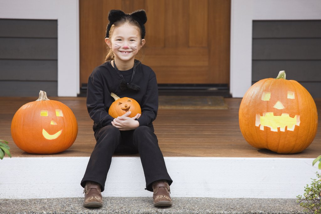 Stock Photo: 1589R-69016 Mixed race young girl in cat costume holding Halloween pumpkin