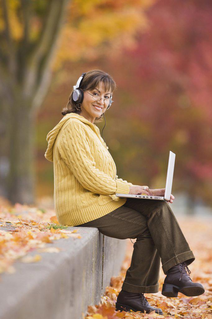Hispanic woman using laptop outdoors with headphones : Stock Photo