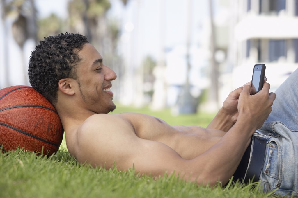 Stock Photo: 1589R-69127 Young mixed race man with bare chest on grass with cell phone