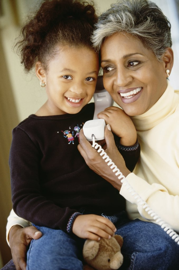 Stock Photo: 1589R-69248 African grandmother and granddaughter using telephone