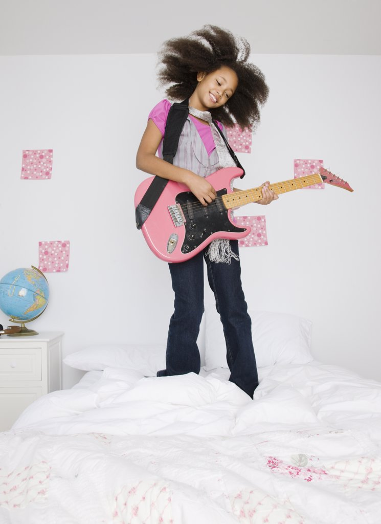 Stock Photo: 1589R-69281 African girl playing guitar on bed
