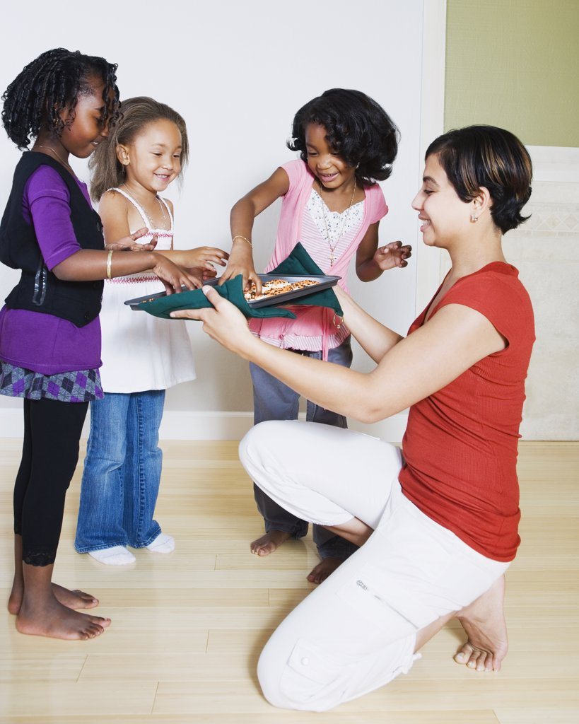 Woman serving cookies to girls : Stock Photo
