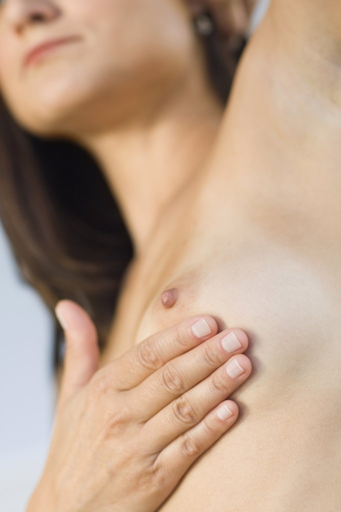 Close up of Hispanic woman doing breast self-exam : Stock Photo