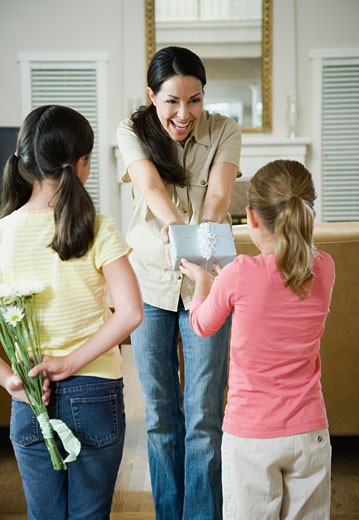 Stock Photo: 1589R-69577 Two daughters giving gifts to mother