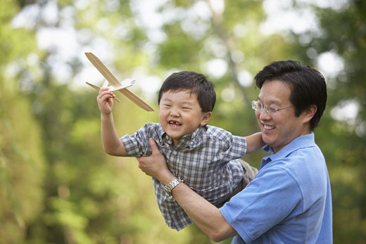 Asian father and son playing with toy airplane : Stock Photo
