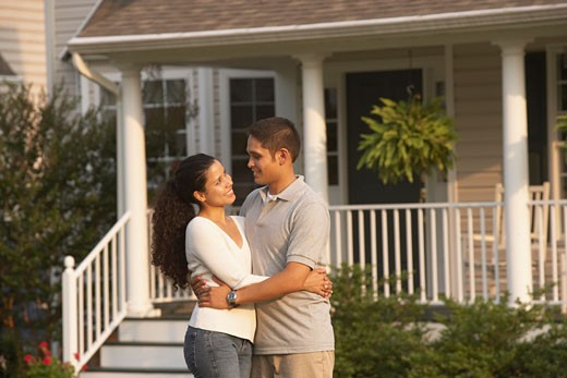 Stock Photo: 1589R-69716 Hispanic couple hugging in front of house