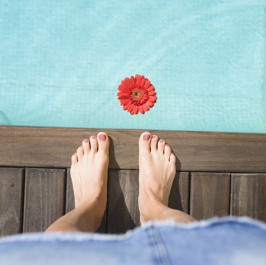 High angle view of bare feet next to flower in pool : Stock Photo