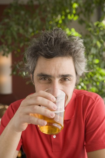 Middle-aged man drinking outdoors : Stock Photo