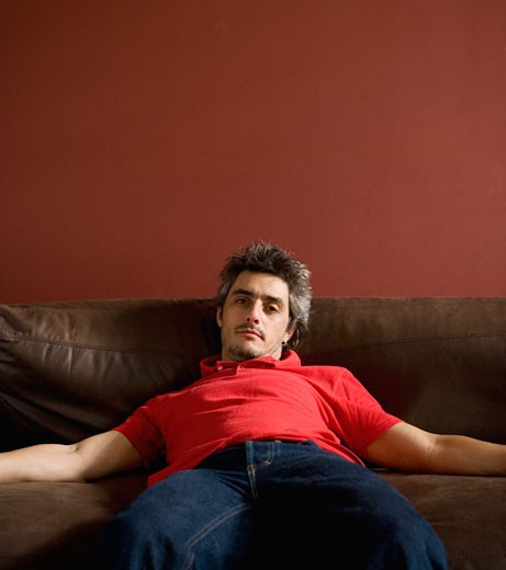 Man slouching on sofa : Stock Photo